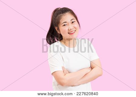 Asian Woman Crosses Her Arms, Nice Smile, Joyful, Happy Feeling, White Shirt, Pink Background