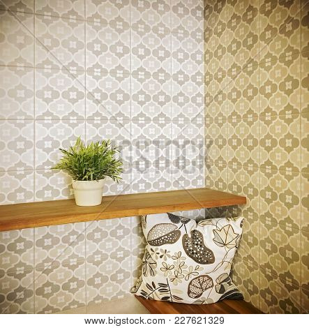 Detail Of An Entrance Hall With Green Plant On A Shelf And Retro Style Wallpaper.