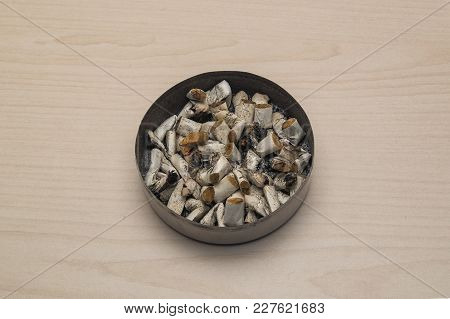 Ashtray And Cigarette Butts Against The Background Of A Light Table