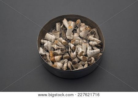Ashtray With Lid And Cigarette Butts Against The Background Of A Gray Table