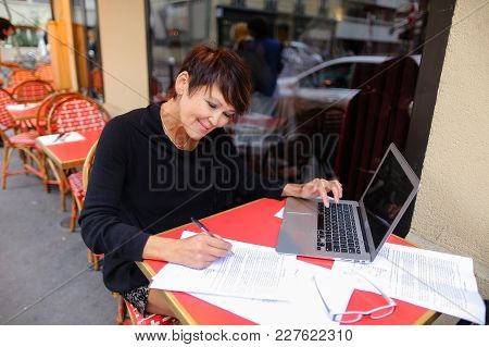 Middle Aged Female Student Using Laptop For Writing A Research Work. Woman Sitting At Red Table In C