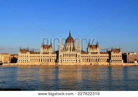 The Hungarian Parliament Building On The Danube River In Budapest, Hungary During The Daytime With A
