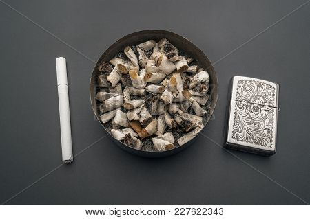 Ashtray With Cigarette Butts Against The Background Of A Gray Table. A New Cigarette And A Gasoline
