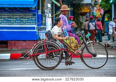 Yangon - Oct 21, 2017: A Tricycle Driver Is Having A Friendly Discussion With His Passenger While Th