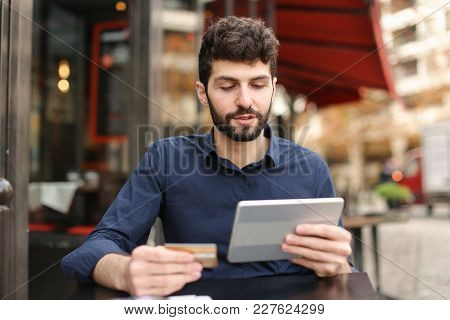Happy Dad Paying With Money Card At Website Store Using Smartphone In  . Young Man Sitting At Street