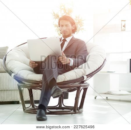 young businessman with laptop sitting in big comfortable armchair.