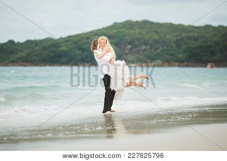 Bride And Groom Hugging At The Sea. Couple In Love On Deserted Beach. Marriage Registration For Coup