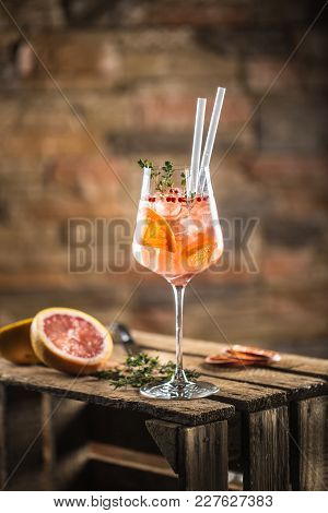 Cocktail Drink On A Old  Wooden Board. Alcoholic Beverage With Tropical Fruits Red Pepper Herb And I