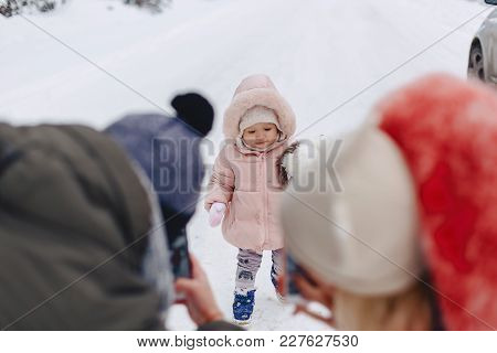 Happy Family Doing A Photo Of Her Little Daughter In The Snowy Picturesque Area Of The Pine Forest O