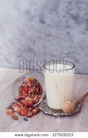 Glass Of Milk And Granola Bowl. Healthy Nuts And Dried Fruits On Rustic Wooden Background.