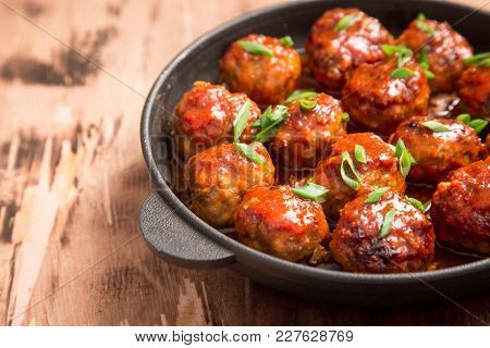Meatballs In Sweet And Sour Tomato Sauce. Homemade Roasted Beef Meatballs In Cast-iron Skillet
