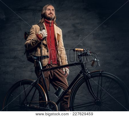 Stylish Bearded Male With Long Hair Holds Backpack And Posing Near Fixed Bicycle In A Studio.