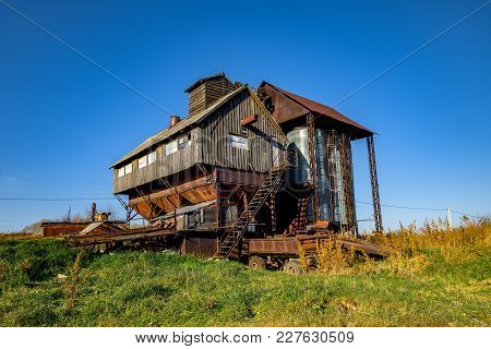 Abandoned Grain Elevator In The Village Against The Blue Sky In Summer