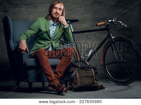 A Casual Bearded Hipster Man In A Green Jacket Sits On A Chair With Single Speed Bicycle On Backgrou