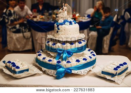 Wedding White Cake Decorated With Blue Roses With Three Tiers And Cakes And A Figure Of The Bride An