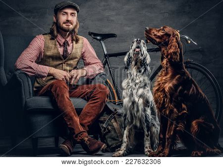 A Stylish Bearded Man In A Cap Sits On A Chair With Two Ireland Setter Dogs And A Bicycle On A Backg