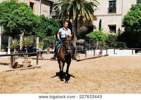 Cordoba, Spain - April 12, 2017: Woman Horse Rider Riding A Brown Andalusian Horse Also Known As Pur