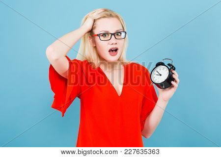 Portrait Of Attractive Surprised Blonde Woman In Glasses And Red Dress Isolated On Blue Background W