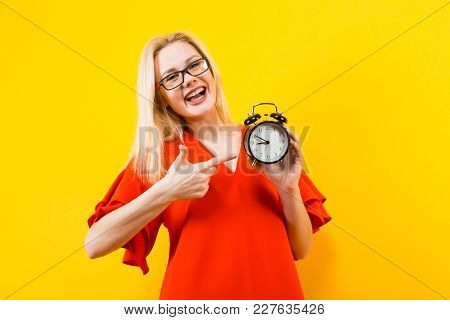 Portrait Of Attractive Cheerful Blonde Woman In Glasses And Red Dress Isolated On Yellow Background
