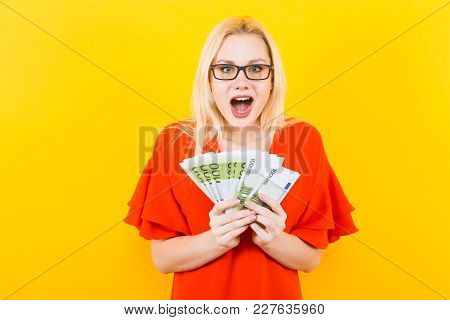 Portrait Of Excited Woman In Glasses And Red Dress Isolated On Yellow Background Hold Fan Of Euro Ba