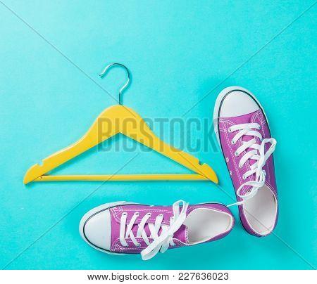 Hanger And Gumshoes On Blue Background