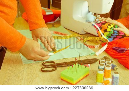 Tailor Hands Working With Measure. Workplace Of Seamstress. Dressmaker Cuts Dress Detail On The Sket
