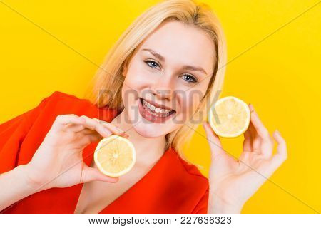 Close Up Portrait Of Attractive Smiling Woman In Red Dress Isolated On Yellow Background Holding Two