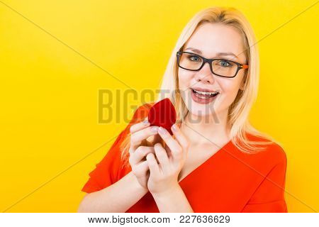 Surprised Happy Attractive Woman In Red Blouse And Glasses On Yellow Backgroung With Copyspace Hold