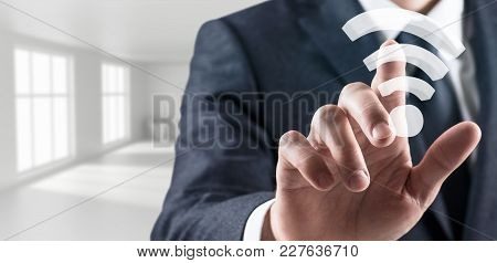 Businessman Touches Wireless Wifi Icon In Bright White Office. 3d Rendering