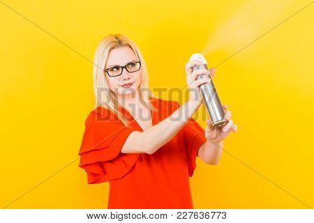 Portrait Of Attractive Blonde Woman In Red Dress And Glasses Isolated On Yellow Background Spraying