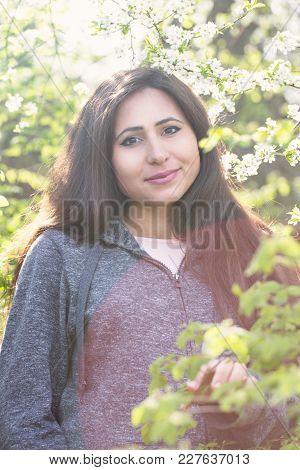 Beautiful Pregnant Woman Near Blooming Spring Tree