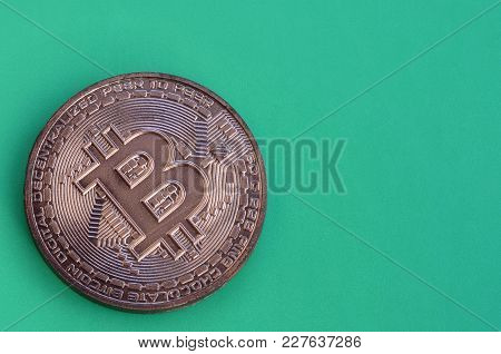 Chocolate Product In The Form Of Physical Bitcoin Lies On A Green Plastic Background. Model Of The C
