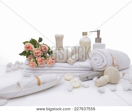 Spa setting with lying on rose with herbal ball , towel, white stones,
