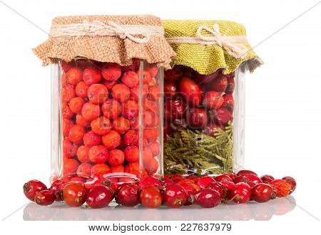 Glass Jars Full Of Berries, Close Scattered Rose Hip Berries Isolated On White Background