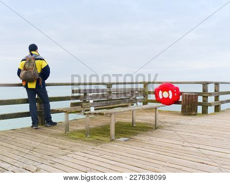 Man Traveler With Green Backpack Sit On Wooden Sea Pier. Man In Trekking Suit In Harbor In Misty Day