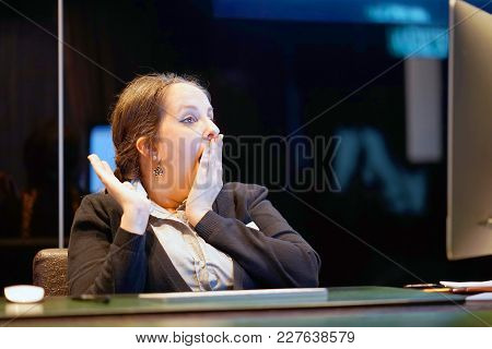 Hotel Manager. A Woman-reception Shocked Sitting In Front Of The Monitor Of Computer. Funny Face Exp