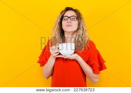 Portrait Of Attractive Curly-haired Woman In Glasses And Red Dress Isolated On Orange Background Wit