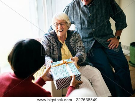 Cheerful senior woman recieving a gift box
