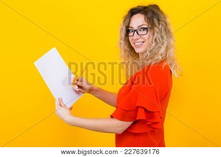 Portrait Of Attractive Curly-haired Businesswoman In Red Dress And Eyeglasses Isolated On Orange Bac