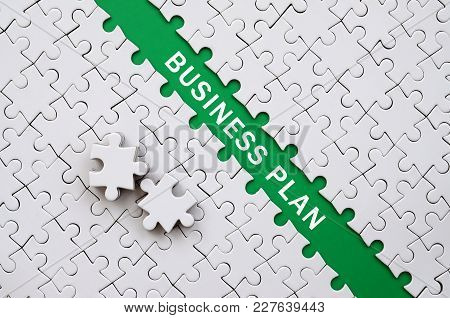 Business Plan. The Green Path Is Laid On The Platform Of A White Folded Jigsaw Puzzle. The Missing E