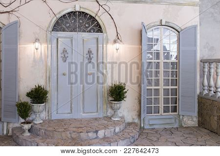 Closed Window And Door With Grey Color Wooden Shutters On An Ocher Color Plastered Wall.  Town Porch