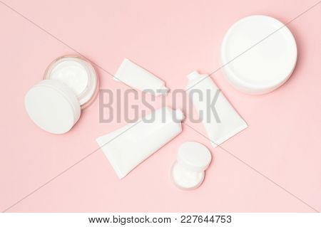 White Cream Containers And Cosmetic Tubes Top View On Pink Background.