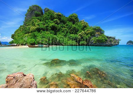 Long Tail Boats By The Shore At Kra Bi Andaman Sea Of Thailand Against Beautiful Clear Blue Sky.