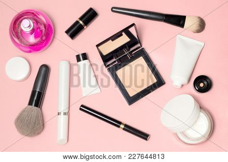Randomly Placed White And Black Cosmetic Supplies Top View On Pink Background. Lipstick, Eyeliner, B