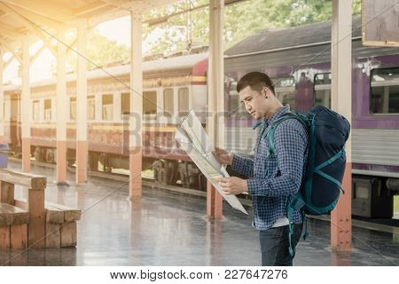 Asian Traveler Man Standing On Platform And Looking At Interesting Places To Travel From Paper Map A