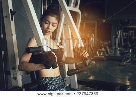 Asian Women Stronger And Pushing Weight Bar At Gym.