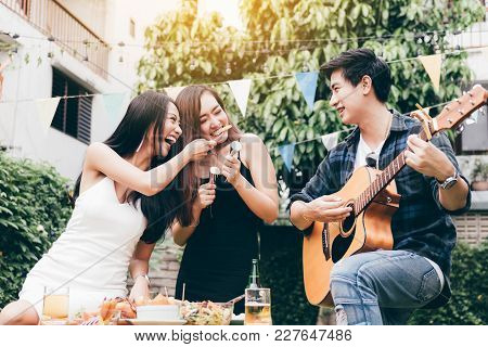 Asian Young Women Feeding To Friend With Guy Playing Guitar Singing At Home Garden Outdoors.