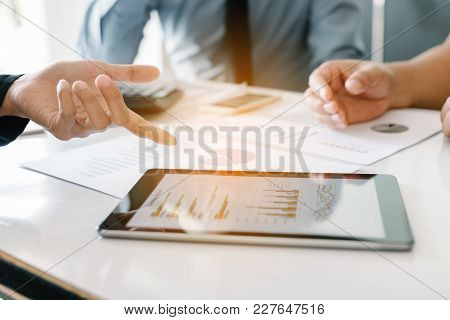 Business People Examining Financial Reports Working On Desk And Analyzing Business Growth On Tablet