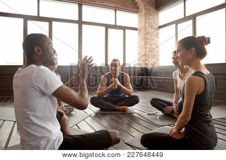 Excited African American Man Talking To Sporty Happy Diverse Friends Sitting On Mat In Studio, Happy