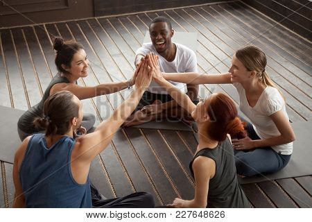 Diverse Happy People Giving High Five Sitting On Mats At Yoga Seminar In Studio, Multiracial Group J